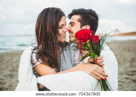 Young couple in love, Attractive man and woman enjoying romantic date at the beach at sunset