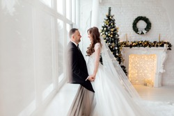 Young couple in love bride and groom posing in studio on background decorated with Christmas tree in their wedding day at Christmas near the large panoramic window. selective focus
