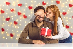 Young couple in love celebrating Saint Valentine's Day or relationship anniversary. Happy woman covering boyfriend's eyes giving him surprise gift. Smiling man getting present from loving girlfriend