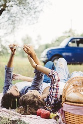Young couple in love doing a picnic outdoors and using a tablet
