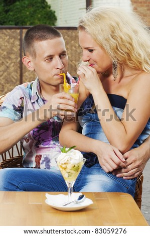Young couple in love drinking juice in the cafe