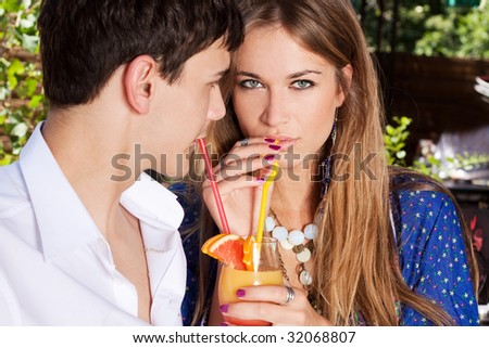young couple in love drinking juice, outdoor shot