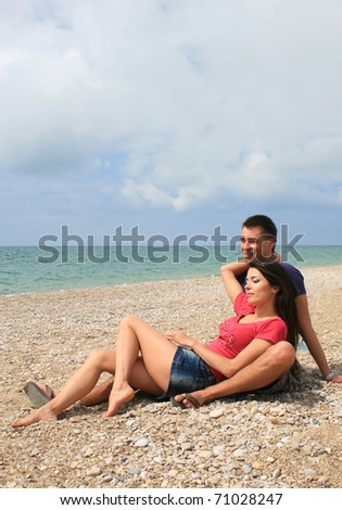 Young couple in love having a good time on a beach