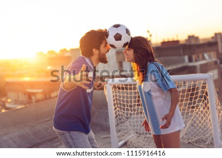 Young couple in love having fun on a building rooftop after playing football, dancing and balancing with the ball between their heads #1115916416