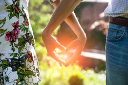 Young couple in love holding hands in the sunset in summer evening. Bright toning picture