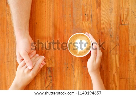 Young couple in love holding hands over red cup of coffee with heart shaped foam latte art on vintage grunged scratched table. Man & woman body language. Background, top view, close up, copy space.