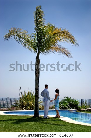 Young couple, in love, holding hands under a palm tree in the sun next to a blue swimming pool in Spain.