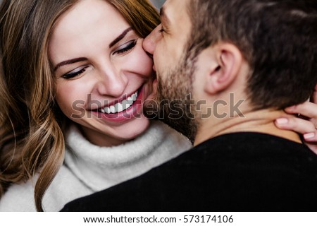 Photo of Young couple in love hug each other on the black background