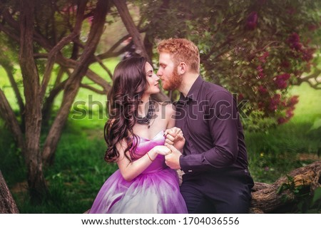 Young couple in love in a lilac garden. Girl in a lilac dress in the bushes of lilac. Red-haired guy in a black suit hugs a dark-haired girl in a luxurious sleeveless dress. Spring lilac blossom