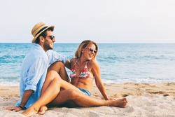 Young couple in love lying on the beach, enjoying