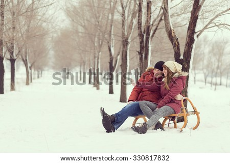 Young couple in love on a winter vacation sitting on a sleigh and making selfie
