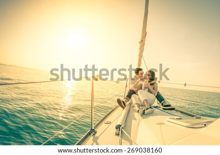 Young couple in love on sail boat with champagne at sunset - Happy exclusive alternative lifestyle concept  - Soft focus due to backlight on vintage nostalgic filter - Fisheye lens and tilted horizon