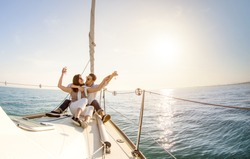 Young couple in love on sail boat with champagne at sunset - Happy people lifestyle on exclusive luxury concept  - Soft backlight focus on warm afternoon sunshine filter - Fisheye lens distortion