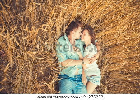 Young couple in love outdoor.in summer in field.Couple hugging.Young beautiful couple in love staying and kissing on the field on sunset Soft sunny colors Beautiful couple lying on the glass