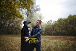 Young couple in love outdoors in the woods walk in nature, beautiful lovers on a sunny day in the forest