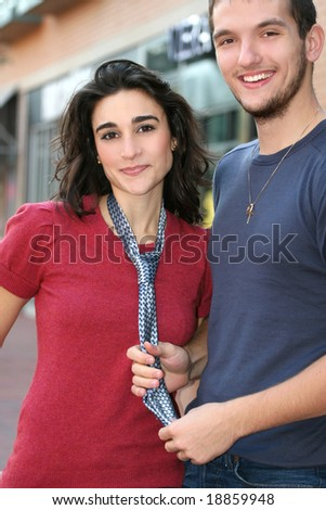 Young couple in love, outdoors - urban /  street setting, posing and having fun