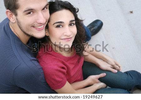 Young couple in love, outdoors - urban /  street setting, posing, hugging, and having fun
