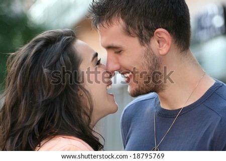 Young couple in love, outdoors - urban /  street setting, posing, kissing, and having fun