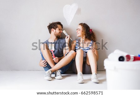 Young couple in love painting walls in their new home. Foto stock ©