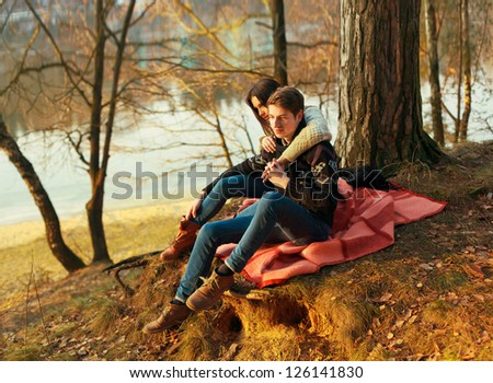 Young couple in love posing in winter. Sensual boy and girl sitting on the ground in spring park