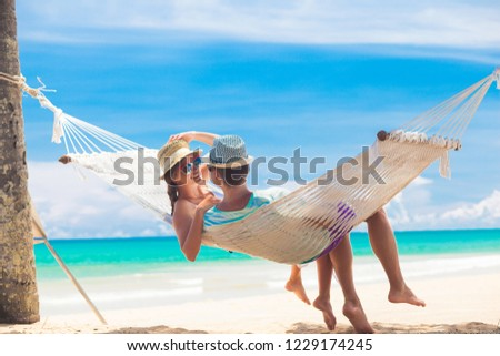 Young couple in love relaxing in a hammock by the beach #1229174245
