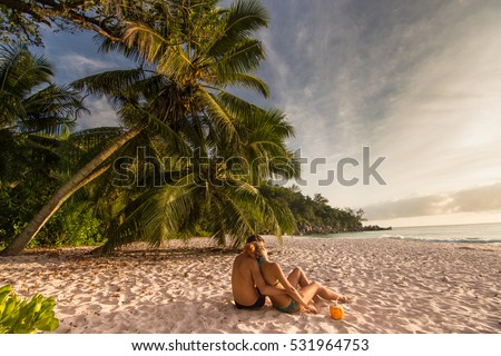 Young couple in love relaxing on exotic beach from Seychelles Islands /  Couple embracing on exotic beach with palm trees and sea looking at sunset / Lovers on exotic beach Anse Georgette , Praslin  #531964753