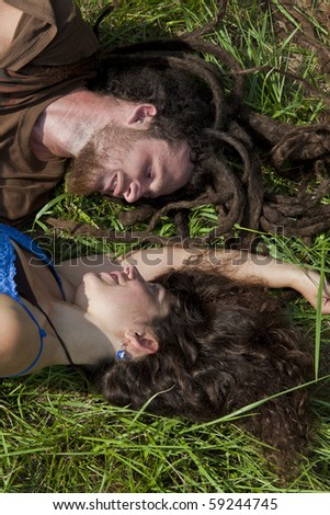 young couple in love resting face to face  on green grass.