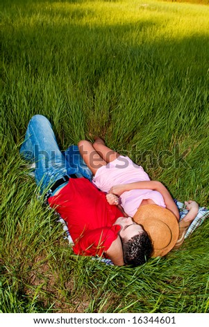 young couple in love resting in a field, summer day