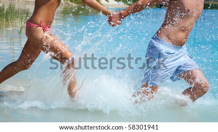 young couple in love running through the water holding hands