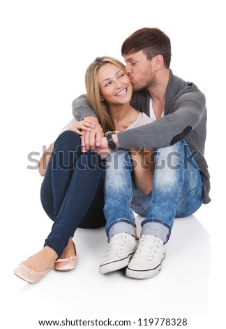 Young couple in love sitting close together on the floor in an affectionate embrace smiling at the camera