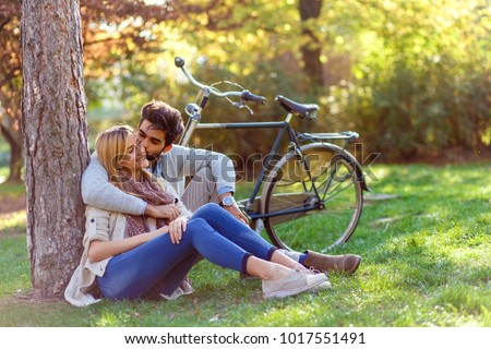 Young couple in love sitting in a autumn park leaning against a tree embracing one another.	 #1017551491