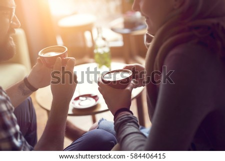 Young couple in love sitting in a cafe, drinking coffee, having a conversation and enjoying the time spent with each other. Selective focus #584406415