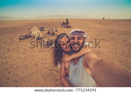 Young couple in love standing near many camels in africa desert taking photo with them, enjoying safari desert