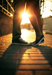 Young couple in love standing on the street in gumshoes in summer sunny warm weather.