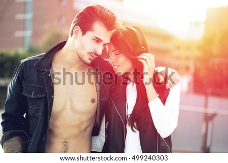 Young couple in love walking in sunset outdoor, first date, listening to music by headphones #499240303