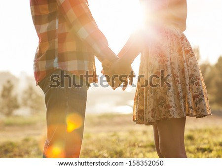 Young couple in love walking in the autumn park holding hands looking in the sunset