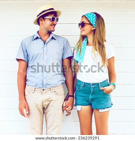 Young couple in love wearing vintage clothing hat and sunglasses, holding hands and posing at white wooden background. Vintage instagram coors.