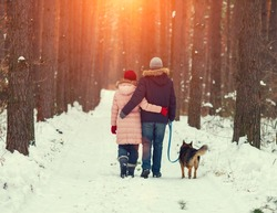 Young couple in love with dog walking in the snowy forest back to camera