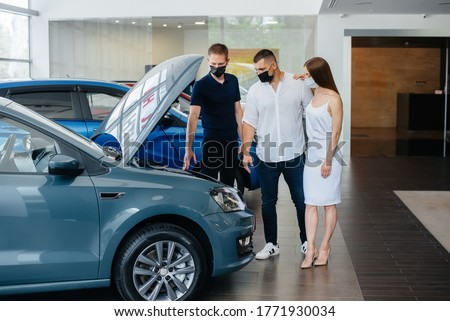 Young couple in masks selects a new vehicle and consult with a representative of the dealership in the period of the pandemic. Car sales, and life during the pandemic