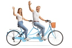 Young couple in matching casual outfits riding a tandem bicycle and waving at the camera isolated on white background