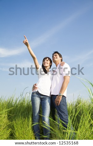 young couple in meadow with hand in air, hugging and smiling. Copy space