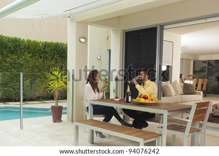 Young couple in modern backyard enjoying champagne and strawberries