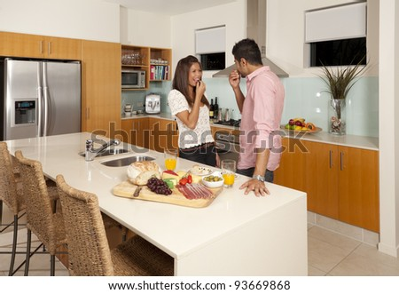 Young couple in modern kitchen with food platter - stock photo