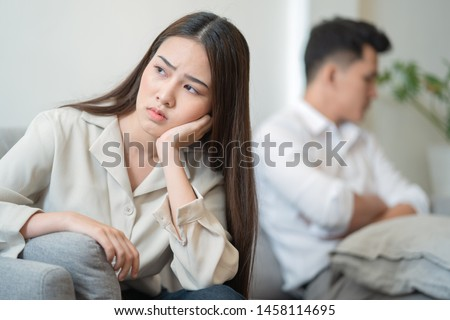 Young couple in quarrel at home.sadness young Asian woman sitting on sofa with boyfriends.relationship problems between couples and communication issues concept #1458114695