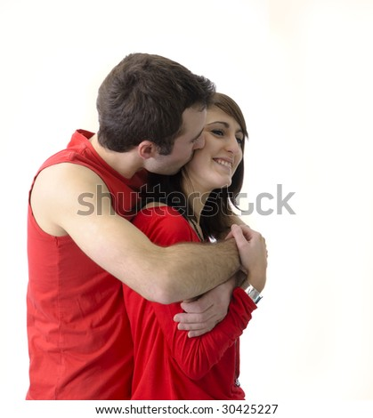 young couple in red holding each other tight on white background