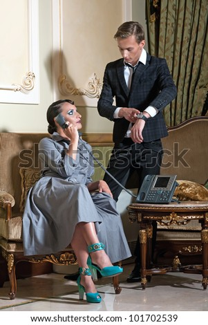 Young couple in royal interior. Woman talking on the phone. Men check his watch.