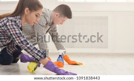 Young couple in rubber gloves cleaning home, washing floor with towel and spray in living-room, copy space. Housekeeping and cleaning service concept #1091838443