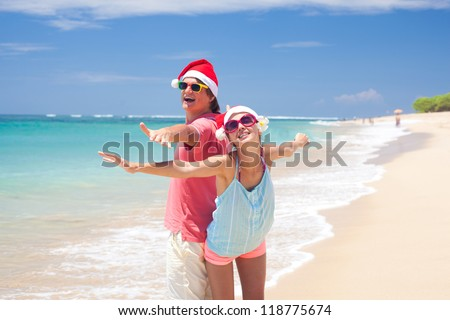 young couple in santa hats having fun on tropical beach. new year