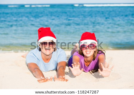 young couple in santa hats laughing on tropical beach. new year
