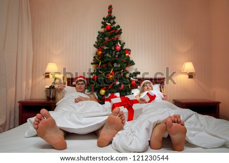 Young couple in Santa's hats  with glass of champagne lying on bed with Christmas tree (Focus on heels)